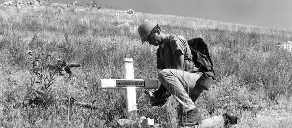 Recreation Guard Fred Patten in the Mann Gulch next to smokejumper Leonard J. Piper's memorial