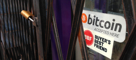 door sign reading 'bitcoin accepted here' behind a security gate