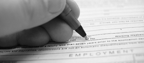 close-up of a hand filling out a job application form