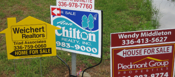 a cluster of real estate for sale signs