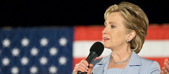 Hillary Clinton in 2008, speaking with a microphone in front of an American flag