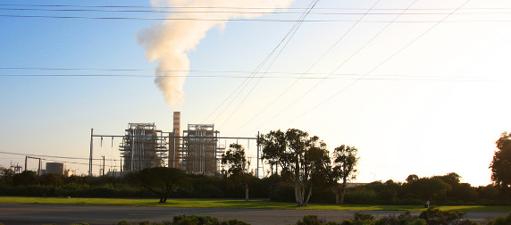 coal-fired power plant on the horizon, emitting smoke against a blue sky