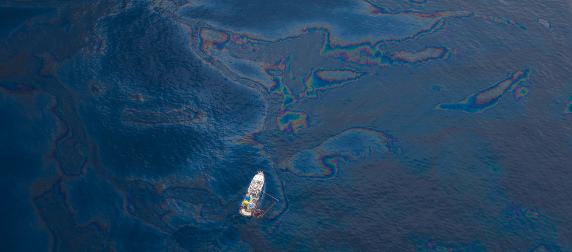 ocean with oil slicks and a boat, viewed from above