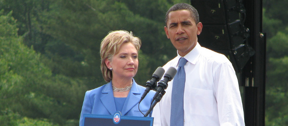 Barack Obama speaks at a podium while Hillary Clinton stands at his side
