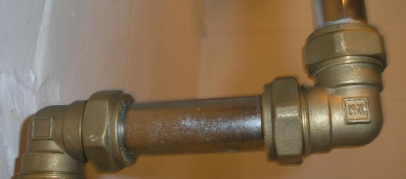 metal plumbing pipes against a white brick wall