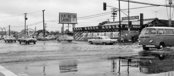 flooding in a parking lot outside a Food Ranch in California circa 1969, with cars and a VW bus
