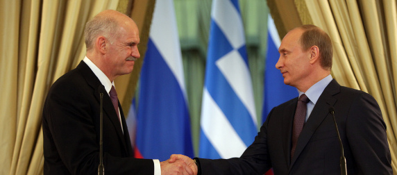 George Papandreou and Vladimir Putin shake hands in front of Greek and Russian flags