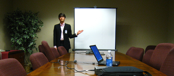 man in a suit standing at the end of a conference table, indicating a black projector screen