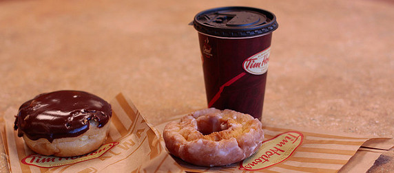 A Tim Hortons coffee cup with lid, next to a cake doughnut and a chocolate frosted filled doughnut