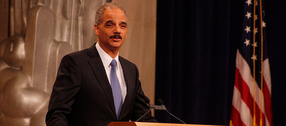 Eric Holder speaking at a podium, an American flag to his left