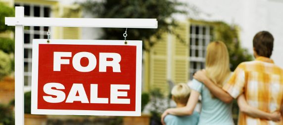 Red 'For Sale' sign, with man, woman and child looking at a house in a blurred background