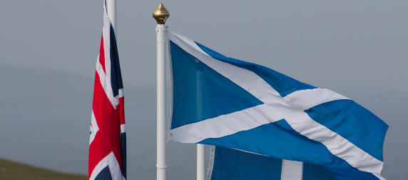 The Union Jack, hanging down, and the Scottish flag unfurled against an overcast sky