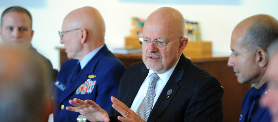 James Clapper, seated at a table with Coast Guard officials