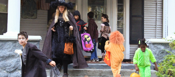 children in Halloween costumes approaching and leaving a front door to trick-or-treat