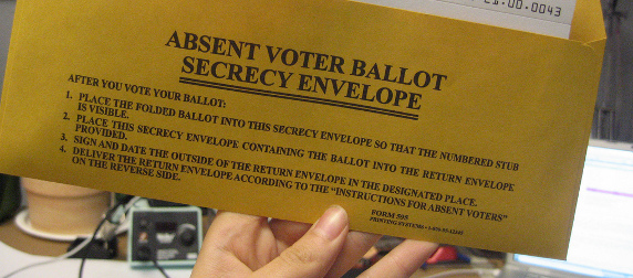 absentee ballot envelope, held up to display instructions on the back