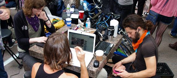 three Occupy Wall Street protestors work on laptops, one of them checking his phone