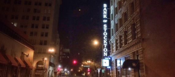 night view of a Stockton, California street including an illuminated sign for the Bank of Stockton