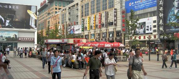 shoppers walking along a busy street in Beijing