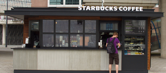 customer with backpack making a purchase at Starbucks in Amsterdam Sloterdijk station