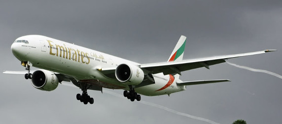 Emirates 777 plane taking off against an overcast sky