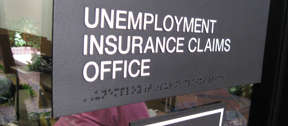 Black sign with white text that reads 'UNEMPLOYMENT INSURANCE CLAIMS OFFICE' with a braille translation beneath