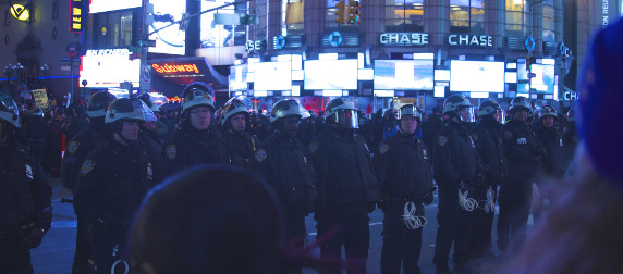 line of NYPD officers face protestors in Times Square