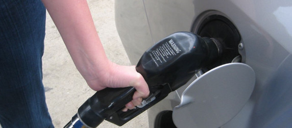 hand holding a gas pump filling the tank of a silver car