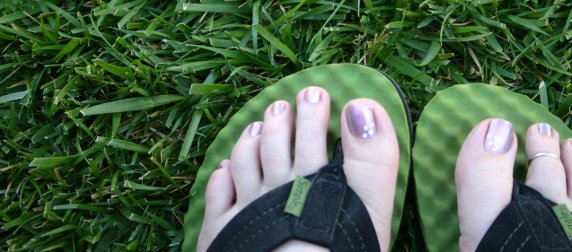 feet with painted toenails in flip-flops against a background of grass