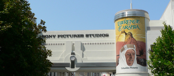 Sony Pictures Studios' entrance, with a column advertising Laurence of Arabia and trees in the foreground