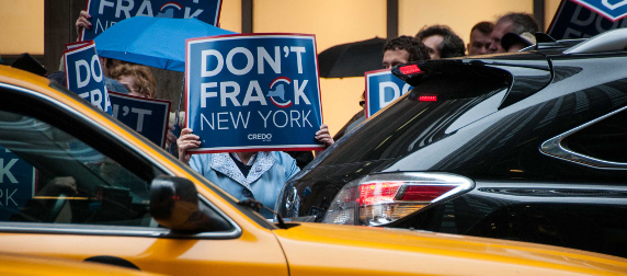 protestor holding a sign reading Don't Frack New York in front of face, viewed across traffic