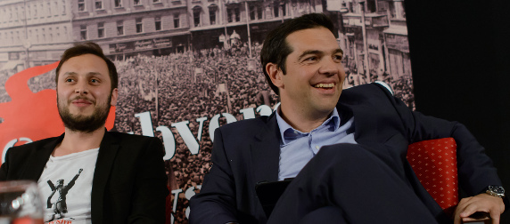 Alexis Tsipras and an unidentified man sitting in front of a banner at the Subversive Festival, Zagreb