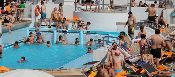 passengers in and around an on-deck cruise ship pool