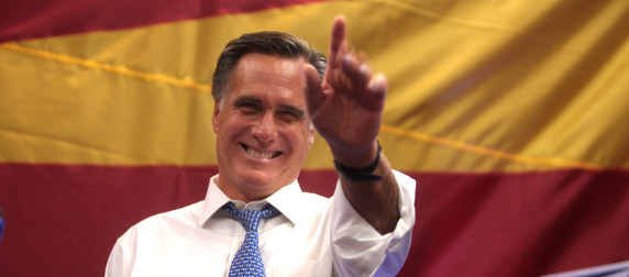 Mitt Romney in front of a red and yellow backdrop