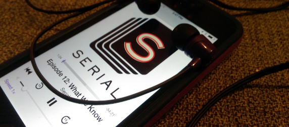 iPhone playing episode 12 of Serial, with earbuds draped over the screen
