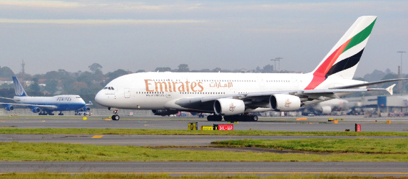 taxiing Emirates A380 jet, with a United airliner in the background