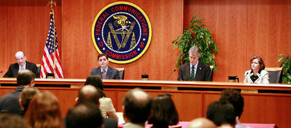 panel seated in front of the FCC seal, viewed from the audience perspective