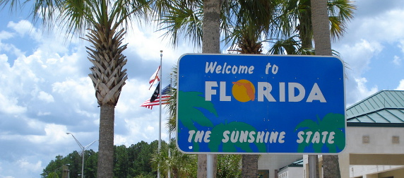 Welcome to Florida sign in front of palm trees, flags and a blue sky