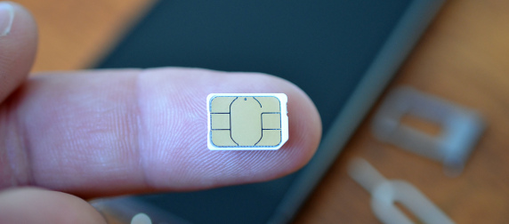 extra-small SIM card on the pad of a person's finger