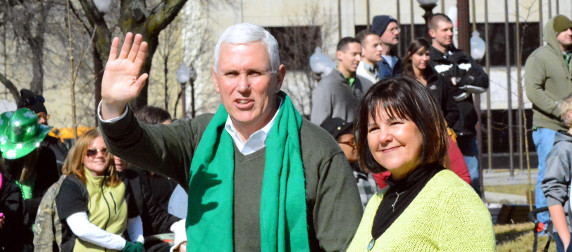 Mike Pence, waving, and Karen Pence at a St. Patrick's Day parade