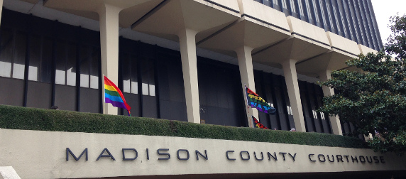 exterior of Montgomery County, Alabama court house, flying several rainbow flags