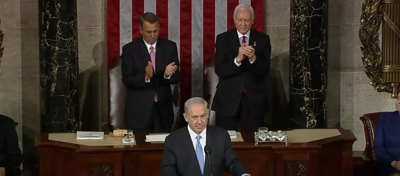 Prime Minister Benjamin Netanyahu at the podium, with John Boehner and Orrin Hatch applauding behind him