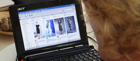person with blond hair looking at dresses in an online store on a laptop computer