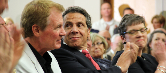 Gov. Andrew Cuomo applauding while looking over his shoulder