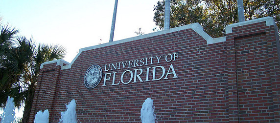 brick University of Florida sign with a fountain in the foreground, palm trees and sky in background
