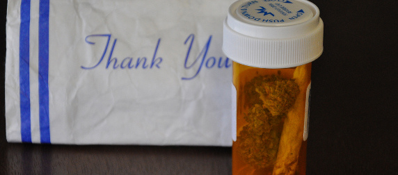 medical cannibis in an orange prescription bottle, in front of a white paper bag that says Thank You