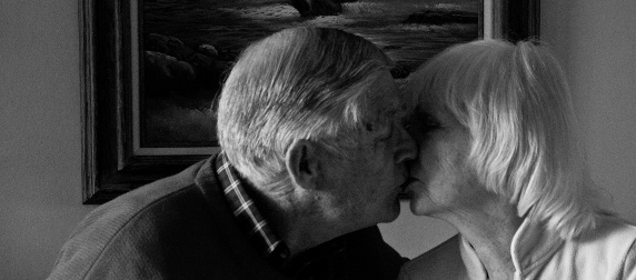 black and white image of older couple in profile, kissing