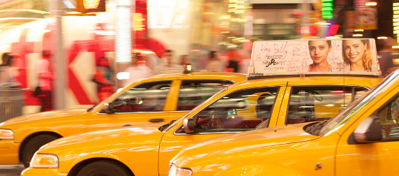three yellow taxis against a blurry urban night scene