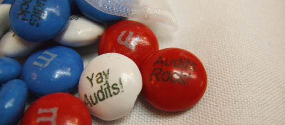 red, white and blue M&M's with custom messages reading Yay Audits! and Audits Rock! against a white tablecloth