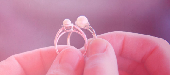 two pearl wedding rings, held against an abstract purple background