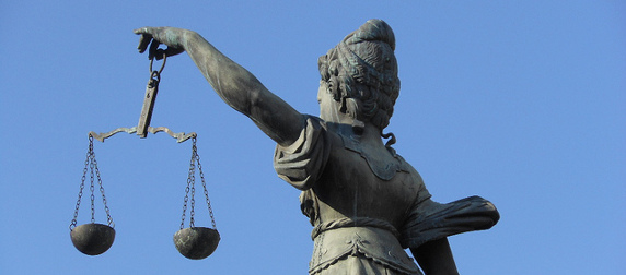 statute of Lady Justice holding scales, viewed from behind against a blue sky